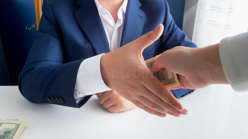 Closeupbild av den fördärvade politikern som skakar handen med personen och mottar mutan arkivfoto