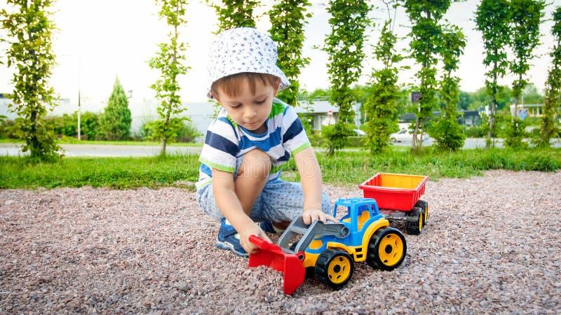 Closeupbild av den gulliga pysen som spelar på palygrounden med leksaker Barn som har gyckel med lastbilen, grävskopan och släpet arkivbild
