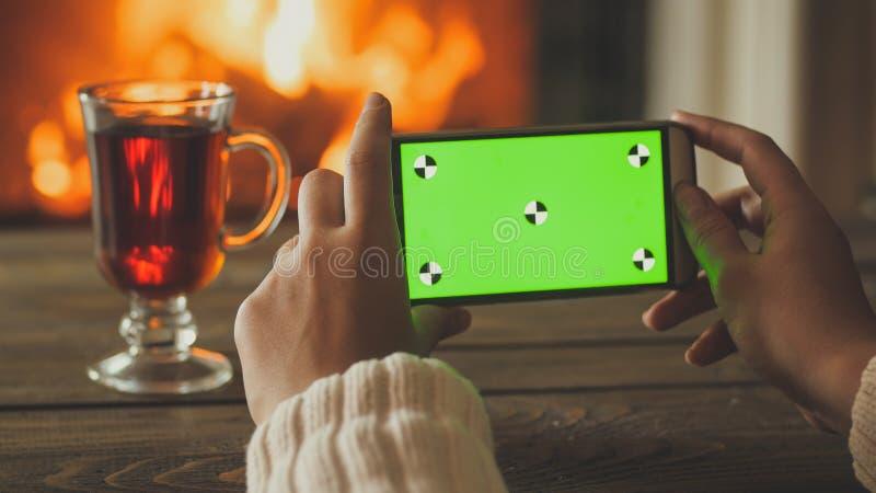Closeupbild av den hållande smartphonen för kvinna och danandefotoet av firepalce på huset Tom grön skärm för att sätta in som är arkivbilder
