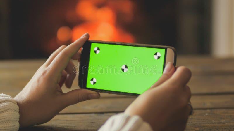 Closeupbild av den hållande smartphonen för ung kvinna och danandebild av den brinnande spisen Tom grön skärm för att sätta in royaltyfri bild