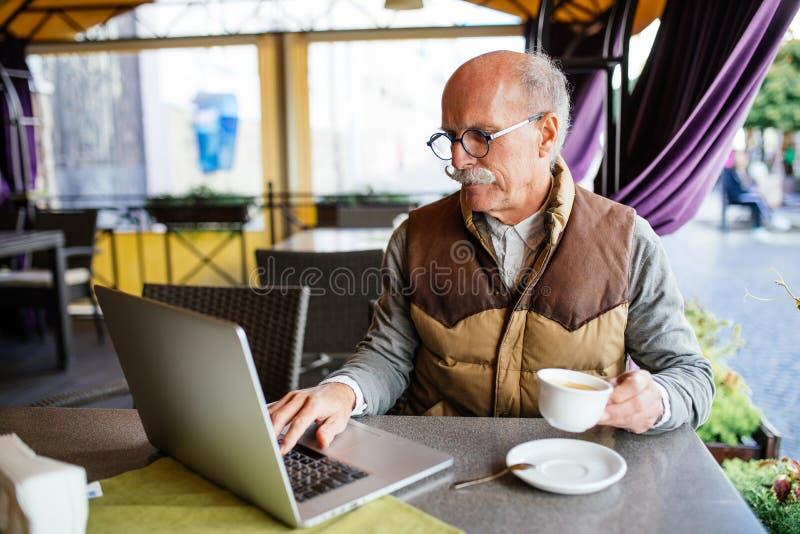 Closeupbild av den höga mannen som använder bärbar datordatoren som tycker om kaffeavbrottet i utomhus- kafé royaltyfri foto