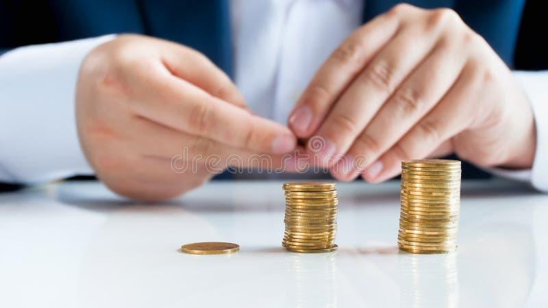 Closeupbild av den manliga affärsmannen som sätter guld- mynt i buntar på det vita kontorsskrivbordet arkivfoto