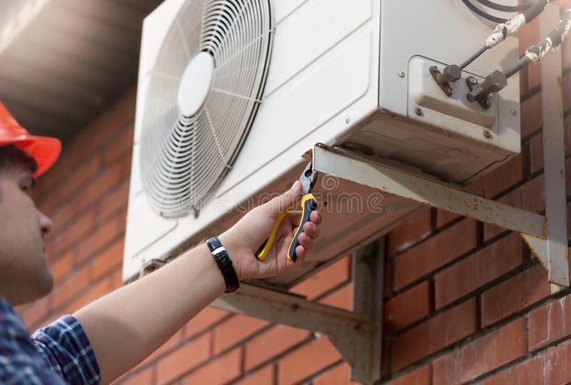 Closeupbild av den manliga arbetaren som installerar luftkonditioneringsapparatenheten royaltyfri fotografi