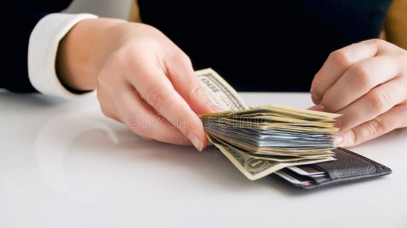 Closeupbild av den unga affärskvinnan som sätter den stora bunten av pengar i läderplånbok arkivbilder