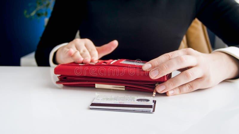 Closeupbild av den unga kvinnan med den stora röda plånboken och kreditkortar royaltyfria foton