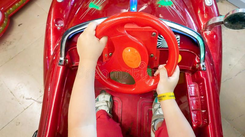Closeupbild av det lilla barnet som rymmer det sterring hjulet i elektrisk leksakbil royaltyfria bilder