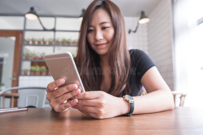 Closeupbild av en härlig asiatisk kvinna med innehavet och att använda för smileyframsida den smarta telefonen royaltyfri bild