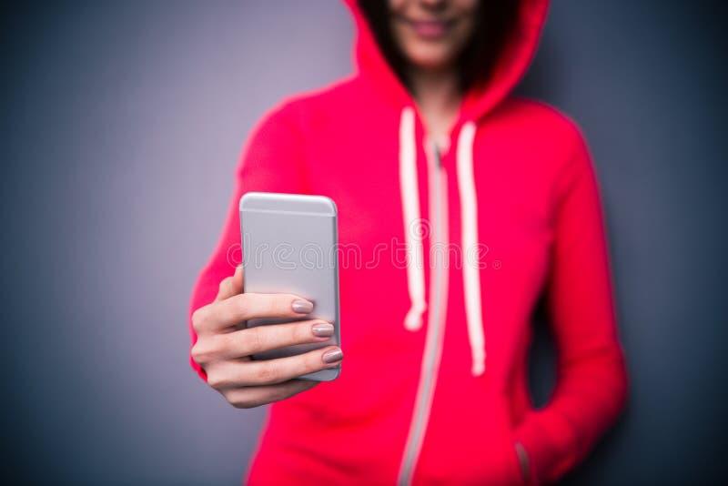 Closeupbild av en hållande smartphone för flicka royaltyfri foto