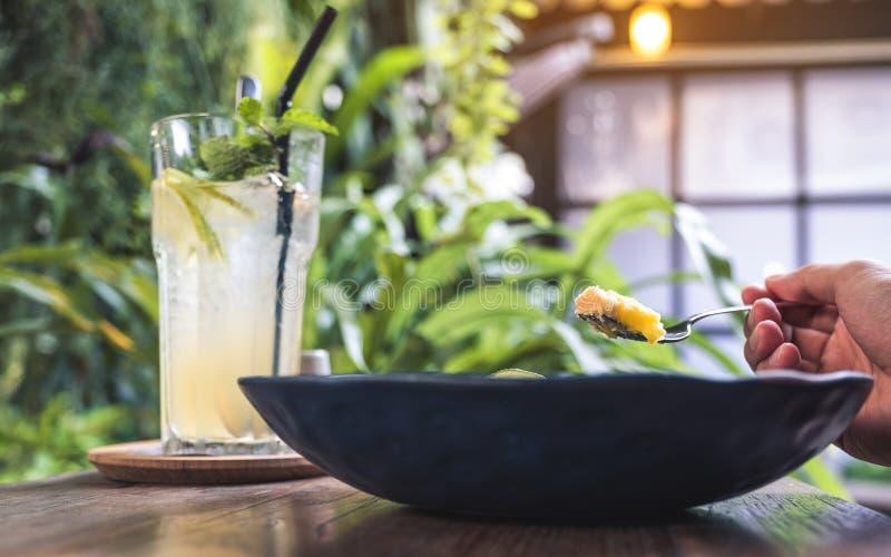 Closeupbild av en hand som kammar hem en gul citronkrämkaka för att äta med gaffeln och citronjuice royaltyfri bild