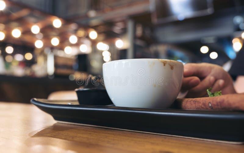 Closeupbild av en kvinna som rymmer en vit kopp kaffe på det svarta tefatet på trätabellen royaltyfria bilder