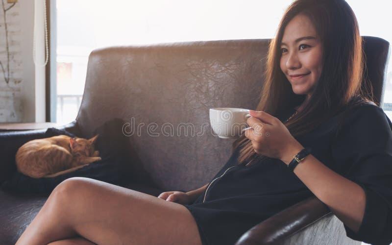 Closeupbild av ett härligt asiatiskt kvinnasammanträde på soffan, medan lite den bruna katten sover fotografering för bildbyråer