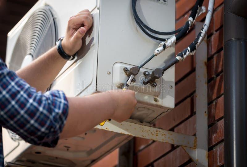 Closeupbild av förbindande rör för manlig tekniker till det utomhus- luftkonditioneringsapparatsystemet royaltyfri bild