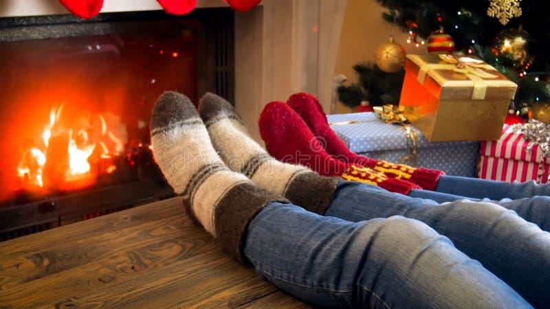 Closeupbild av familjen i woolen sockor som ligger bredvid julgranen och värme vid spisen royaltyfri fotografi