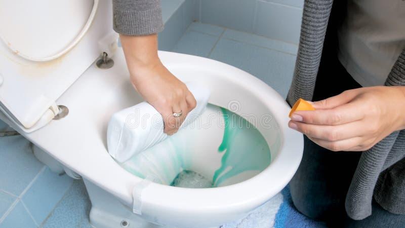 Closeupbild av flytande för lokalvård för ung kvinna hällande antibacterial i toalett royaltyfri fotografi