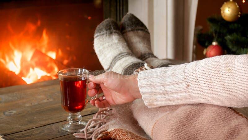 Closeupbild av kvinnan som dricker funderat vin i vardagsrum y spisen royaltyfri bild
