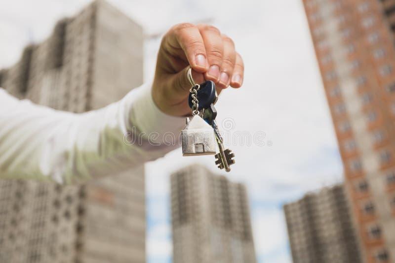 Closeupbild av manliga handinnehavtangenter från nytt hem Begrepp av fastighetsinvesteringen royaltyfri fotografi