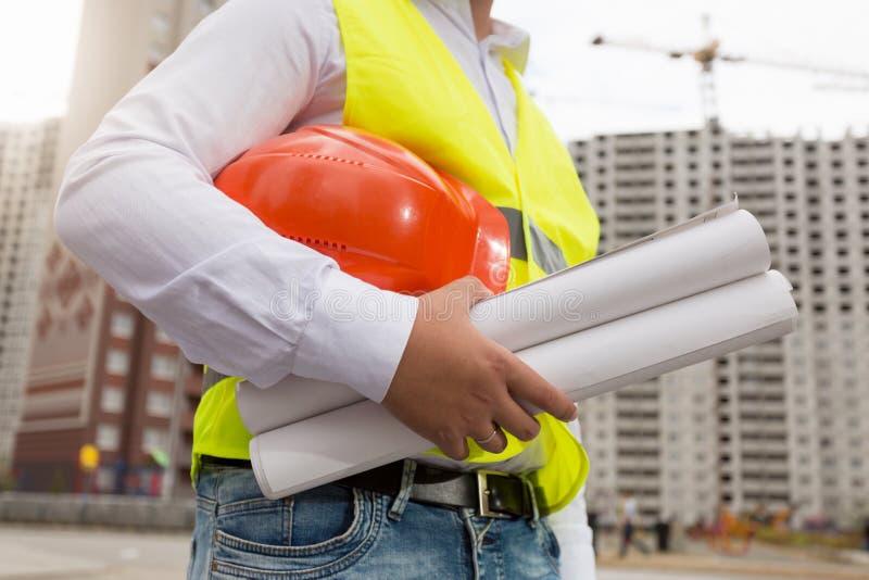 Closeupbild av manliga teknikerinnehavritningar av det nya huset och den röda hardhaten fotografering för bildbyråer
