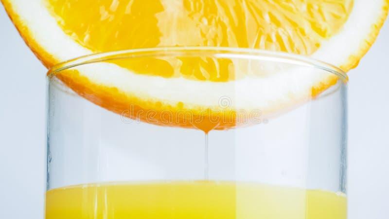 Closeupbild av ny fruktsaft som flödar från orange halva i genomskinligt exponeringsglas royaltyfri fotografi