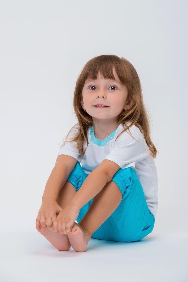 Closeupbild av tillfälliga kläder för nätt liten flicka som sitter på golvet i blå byxa och vita t-skjortan som isoleras på vit royaltyfria foton