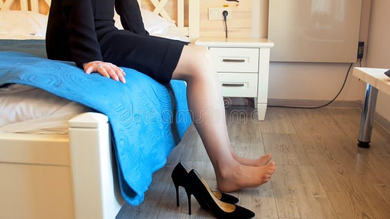 Closeupbild av ungt elegant barfota kvinnasammanträde på säng och sträckningsben arkivbild