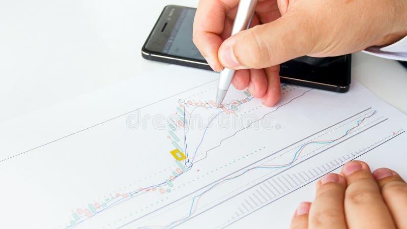 Closeupbilden av affärsmannen som analyserar materielförsäljningar, klassar genom att använda den finansiella grafen fotografering för bildbyråer
