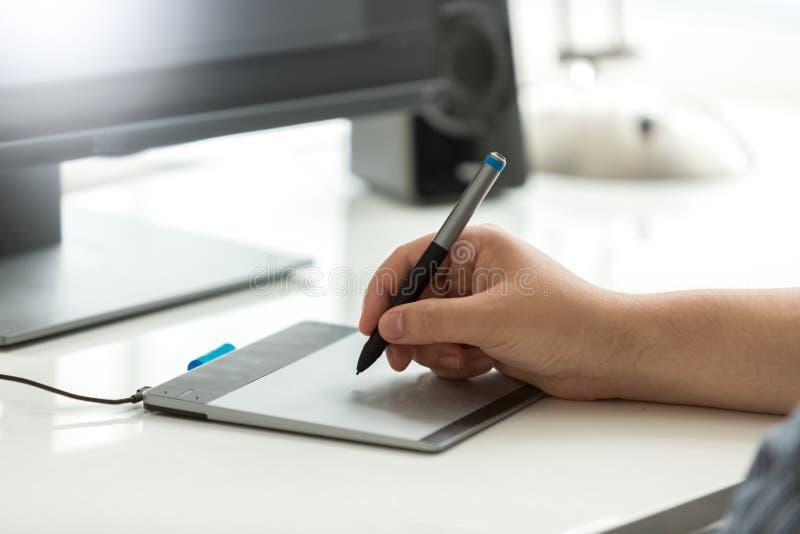 Closeupbilden av den hållande nålteckningen för den manliga handen skissar på den grafiska minnestavlan fotografering för bildbyråer