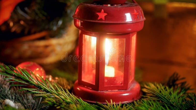 Closeupbilden av den röda brinnande lyktan med stearinljuset på tabellen dekorerade för jul royaltyfri fotografi