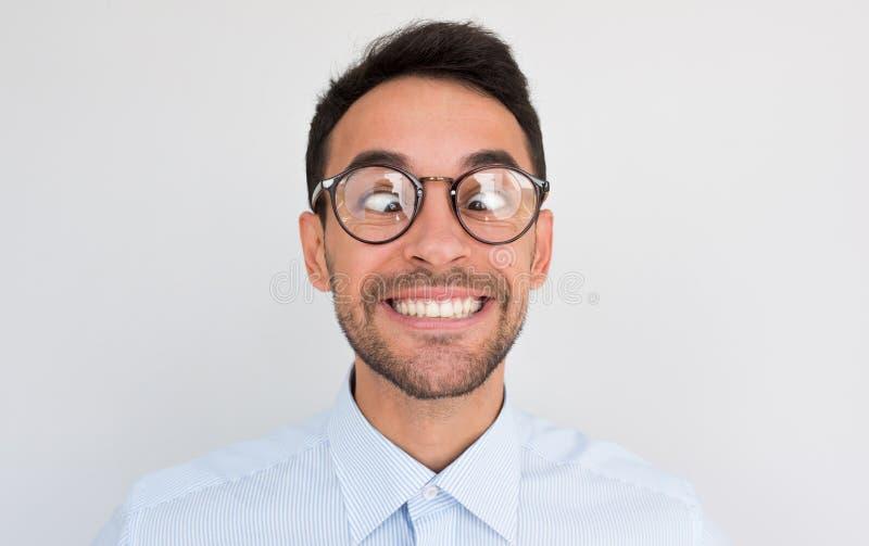 Closeupbilden av den roliga komiska mannen korsar ögon som ler, gör grimasen Den korkade manliga nerden med konstigt uttryck har  royaltyfri fotografi