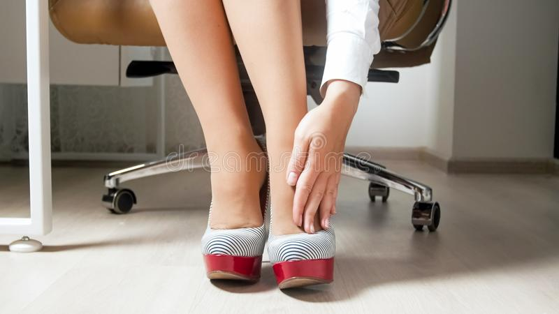 Closeupbilden av den unga busineswomanen som masserar henne, tröttade ben i regeringsställning arkivbild