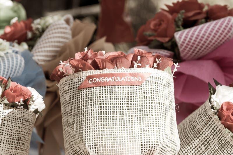 Closeupbukett av den färgrika konstgjorda blomman med ordet CONGRATU arkivfoton