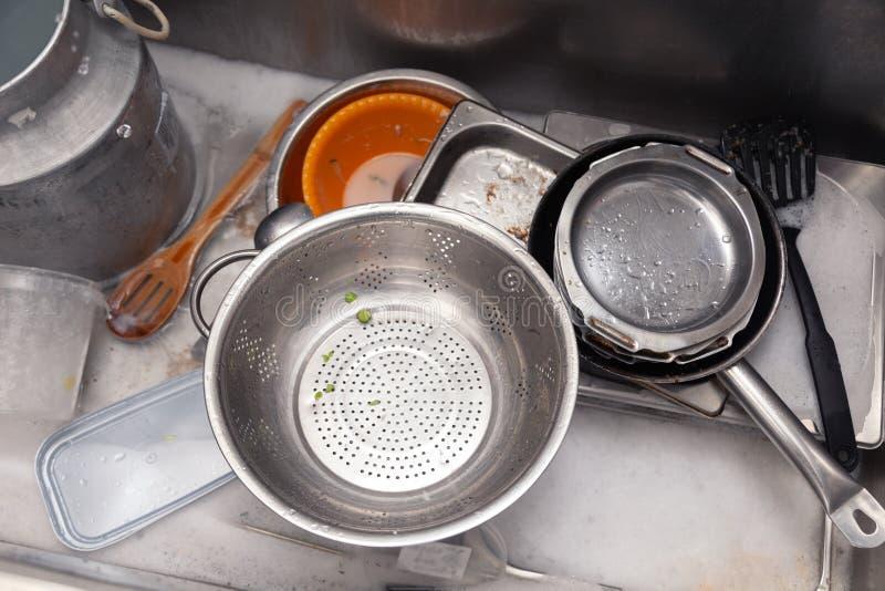 Closeupbunt av smutsiga redskap i metallfyrkantvask på yrkesmässigt restaurangkök: bunt av pannor, durkslag, skyffelvattenkran, royaltyfria foton