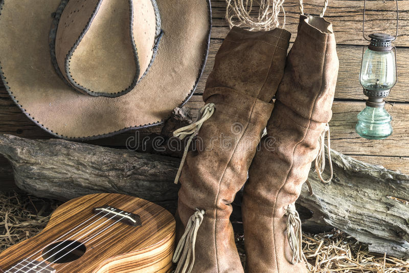 Closeupcowboyhatt och kängor med ukulelet i ladugårdstudio arkivfoto