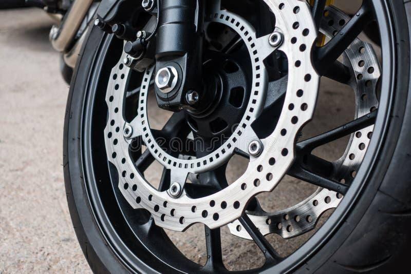 Closeupdetalj av den tävlings- motorcykelskivabromsen med ABSsystemet och gummihjul på vägen arkivbilder