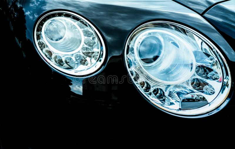 Closeupdetalj av LED bilen för billyktalyx Härlig modern eleganspannlampabil Svart bil Bilindustri royaltyfria bilder
