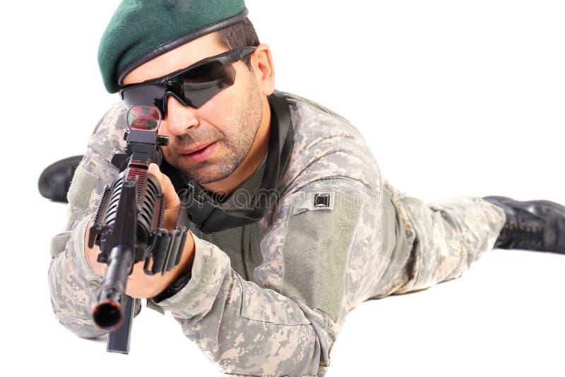 Closeupen av barn tjäna som soldat eller prickskytten som siktar med ett gevär royaltyfri foto