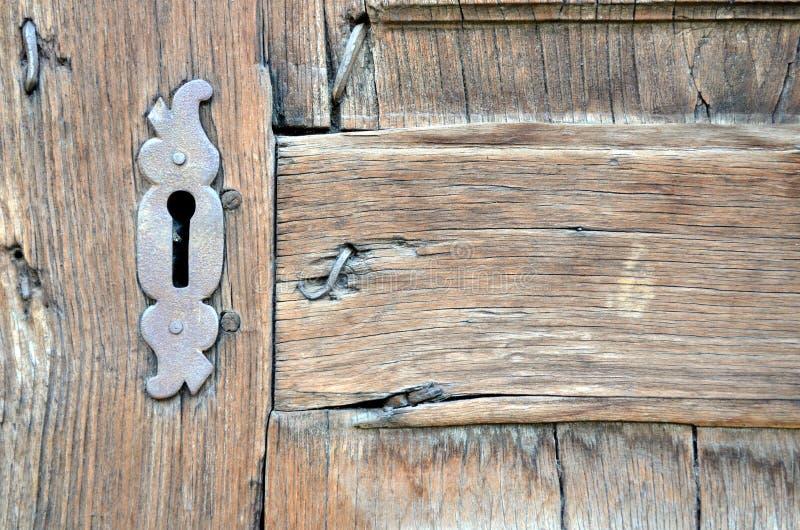 Closeupen av den antika trädörren med den metalliska nyckelhålet och spikar arkivfoton