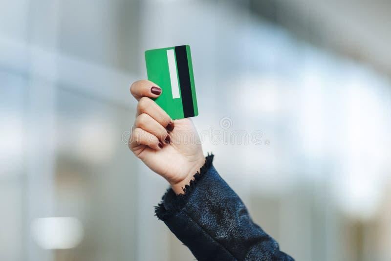 Closeupen av den gröna kreditkorten holded vid kvinnahanden arkivbild