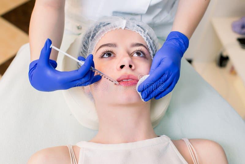 Closeupen av den härliga Caucasian kvinnan får injektionen i hennes kanter arkivbild