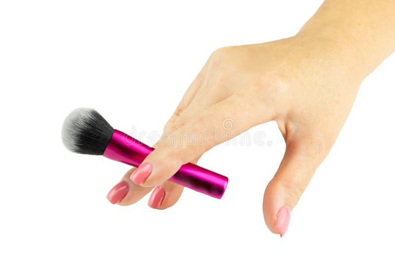 Closeupen av den kvinnliga handen är den hållande yrkesmässiga makeupborsten lura fotografering för bildbyråer
