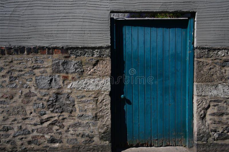 Closeupen av den ljusa blåa dörren på mång- texturerad betong/stenar väggen i UK royaltyfri foto
