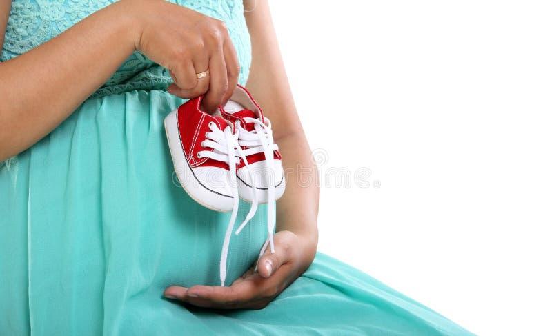 Closeupen av det gravida innehavet för handen för mamma` s behandla som ett barn skor arkivfoton