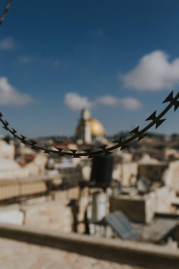 Closeupen av en kedja i fokus med den gamla staden i Jerusalem, Israel gjorde suddig i bakgrunden royaltyfria foton