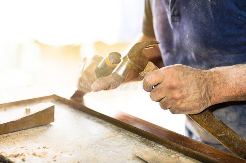 Closeupen av en snickare räcker arbete med en stämjärn och en hammare på träarbetsbänken arkivfoton
