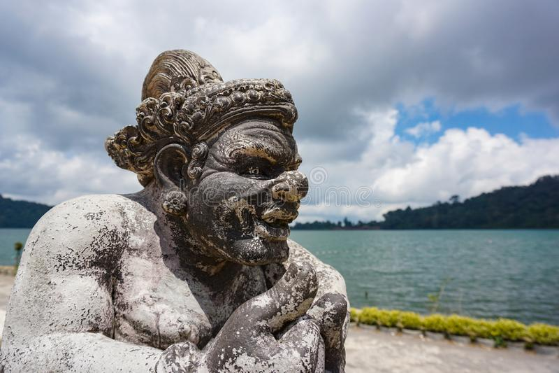Closeupen av en sten för halvt format sned statyn som visar en krigaregud i den hinduiska templet för balinesen, Bali, Indonesien royaltyfri bild