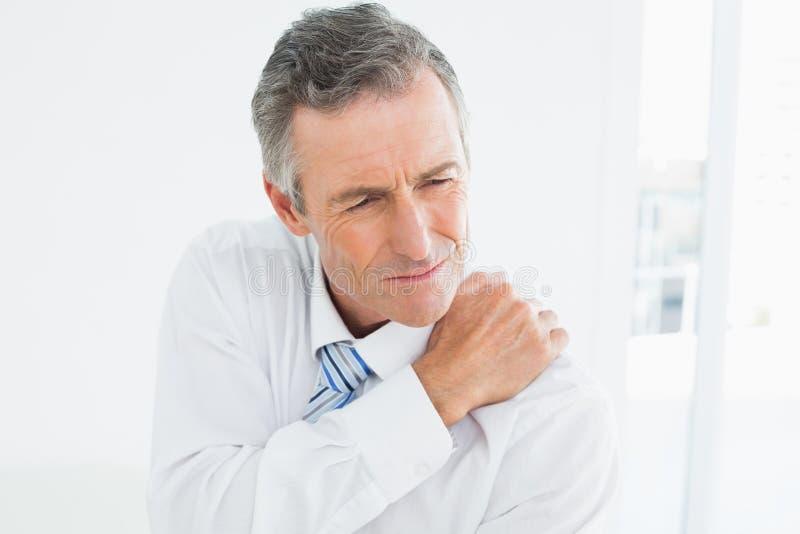 Closeupen av ett moget manlidande från skuldra smärtar royaltyfri bild