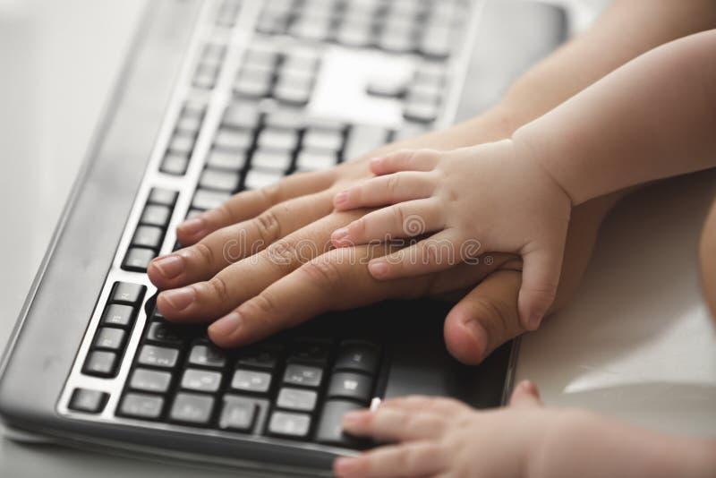 Closeupen av fäder och behandla som ett barn händer för ` s på datortangentbordet royaltyfri bild