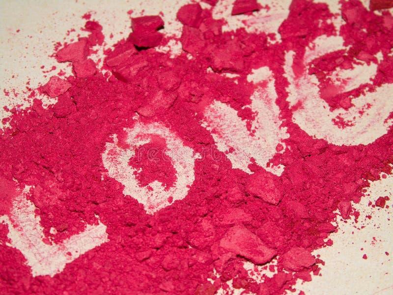 Closeupen av förälskelse som är skriftlig vid rött ögonskuggapulver, utgör, glamour, berlock, mode arkivfoton