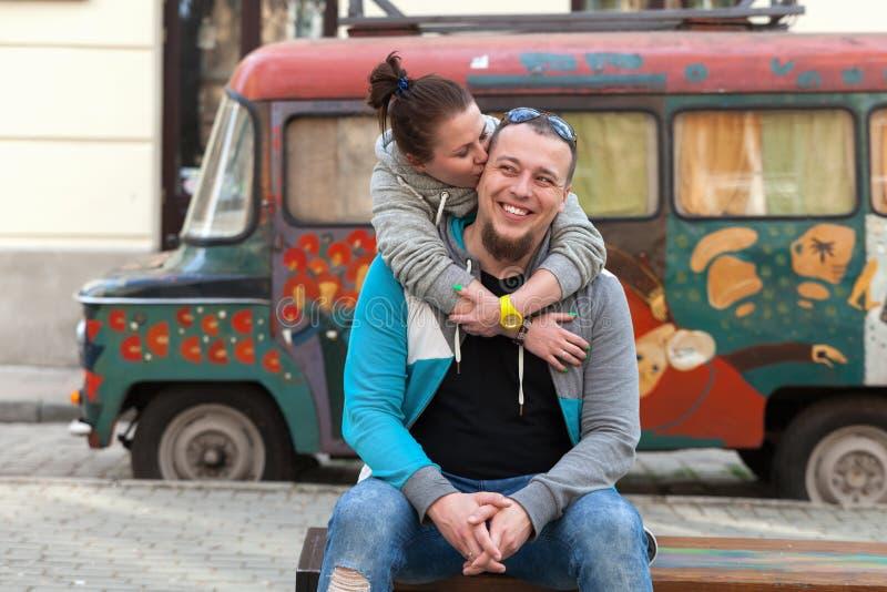 Closeupen av familjpar near den gamla bilen för färgrik paintyng eller zigenarehippieskåpbilen Det lyckliga romantiska barnet kop royaltyfria bilder