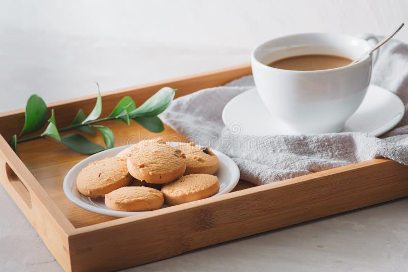 Closeupen av kaffe med mjölkar i den vita koppen och smakliga kakor Skott på ljus stenbakgrund arkivfoton