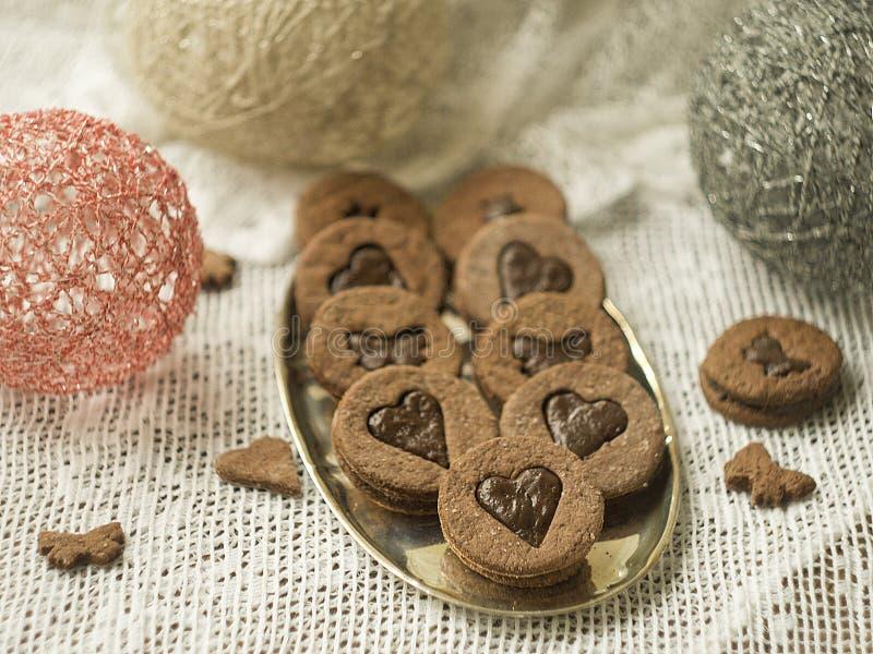 Closeupen av kex och kakor i hjärtaform med karamell som fyller i metallbunke på trätabellen med, snör åt tyg Kakor för arkivbilder